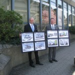 Unser Bild zeigt Ralf Löbach und Andre Schmeis, Vorstand der Bank. Sie zeigen Tafeln mit Bildern des geplanten Umbaus in Much.