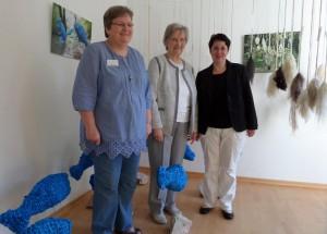 """© M. Lange, 2015 Petra Weise, Christel Walter & Silke Bosbach (von li nach re) in der Premierenausstellung vor der Siegerarbeit """"Forelle Blau"""" von A. Siegburg"""